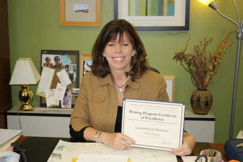 Dr. Kirsten Benson holding the Writing Program Certificate of Excellence awarded to our First-Year Writing Program by Conference on College Composition and Communication's (CCCC).